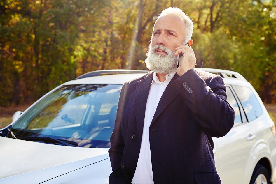 bearded senior man talking on the phone over white car at outdoor